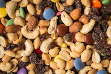 Close up of pile of trail mix with nuts, raisins, and candy