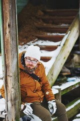 Young good-natured bearded man with glasses and warm clothes is sitting near an old abandoned wooden building in the winter.