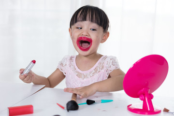 Asian Chinese little girl having fun with mess lipstick