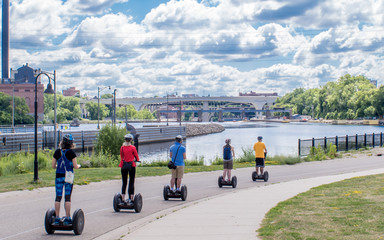 People are riding Segway along Mississippi River