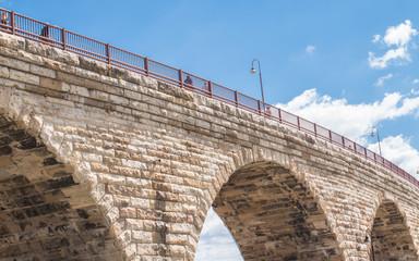 A stone bridge is under blue sky