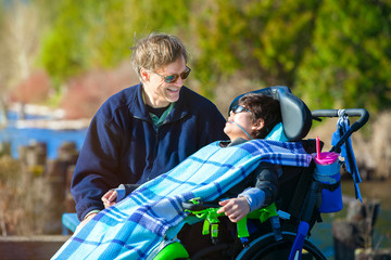 Disabled boy in wheelchair talking with father at lakeside park