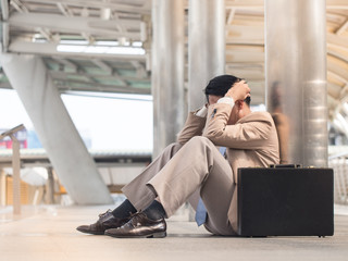 Asian businessman in a suit is worried and stressed  sitting outside office with black briefcase. Unemployment or economy concept.
