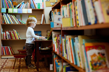 Little boy reading a book in the library.