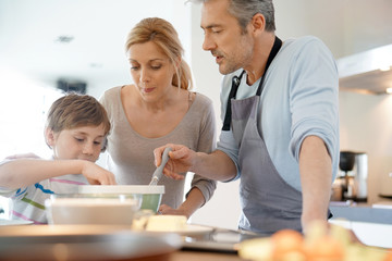 Family cooking together in modern home kitchen