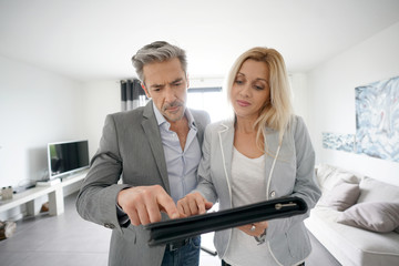 Real-estate agent with client visiting modern house
