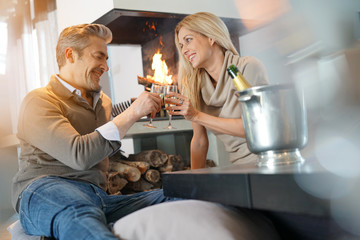 Couple at home cheering with champagne by fireplace