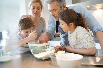 Family baking cake together in home kitchen
