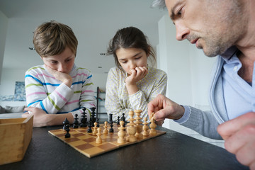 Family playing chess game at home