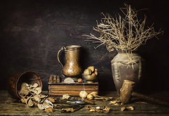 Classic still life with dry plants placed in old vase,copper jar,dry leaves,magazine,cigar,wooden hammer,vintage box and nuts on rustic wooden background.