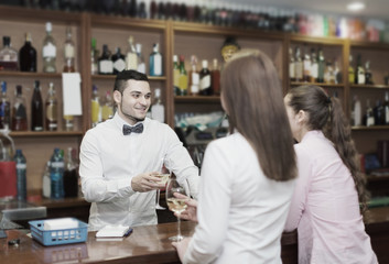 Young bartender and smiling women
