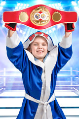 Little boy boxer holding Boxing championship belt.The athlete in scrubs in the background of the ring.Little champion.