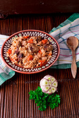 Pilaf on the brown plate on a wooden table, background. Rustic style