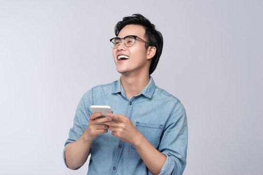 Smart casual asian man using smartphone in studio background