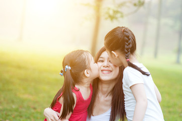 Daughters kissing mother.