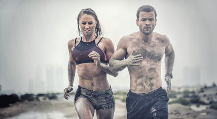 Muscular male and female athlete covered in mud running down a rough terrain with a desert...