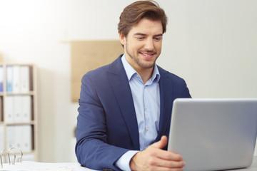 lächelnder mann im büro schaut auf sein notebook