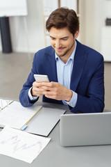 zufriedener geschäftsmann liest eine nachricht an seinem mobiltelefon