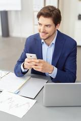 zufriedener geschäftsmann sitzt am schreibtisch und hält sein mobiltelefon in der hand