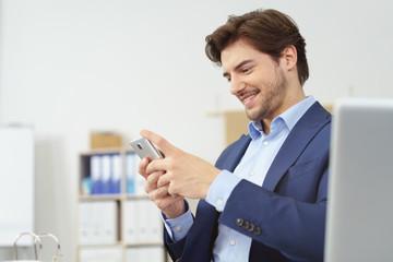 geschäftsmann sitzt am schreibtisch und schaut zufrieden auf sein mobiltelefon
