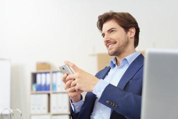 erfolgreicher manager sitzt am schreibtisch und hält sein mobiltelefon in händen