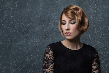 classical portrait of elegant blonde woman with a wave hairstyle and makeup on textural background