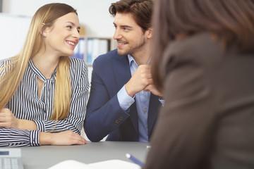 glückliches junges paar in einer besprechung bei der bank