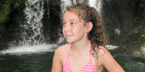 beautiful girl child in front of a waterfall during the summer holidays