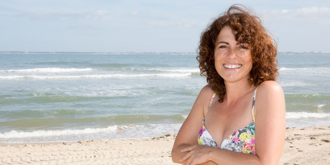 beautiful middle-aged woman with curly hair on the beach in summer