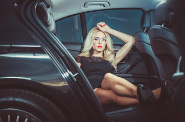 Glamorous blond babe standing near tuned supercar