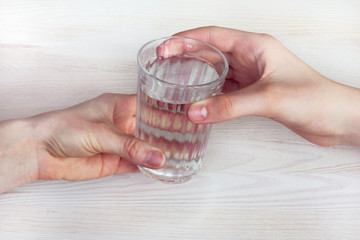 vital valuable resource/ One glass of drinking water is passed from hand to hand