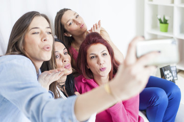 4 beautiful women having fun and taking selfie