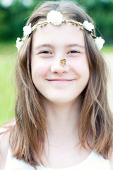 Summer surprise. Girl with floral headband on head and butterfly on nose.