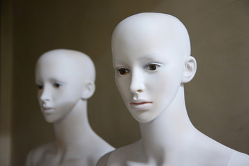Female white mannequins with human faces stand side by side