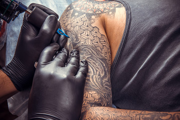 Tattoo specialist makes tattoo pictures in tattoo parlor
