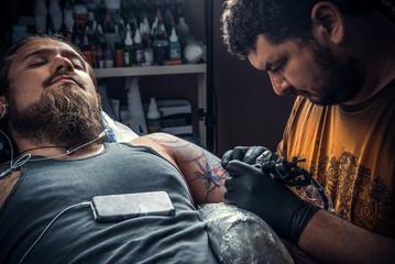 Professional tattooist works in studio