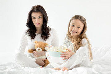 Adorable daughter and mother sitting on bed with marshmallows at home