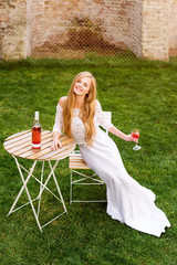 Beautiful woman drinking wine in outdoors cafe. Portrait of young blonde beauty in the vineyards having fun, enjoying a glass of wine in the garden or tasting alcohol cocktail at dining table in lawn.