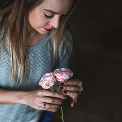 Florist at work: pretty young blond woman holds fashion modern bouquet of different flowersv