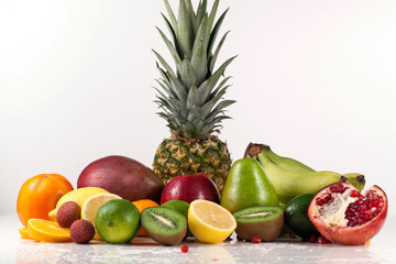 Assorted tropical fruits. Half of pomegranate. Composition placed on a white background