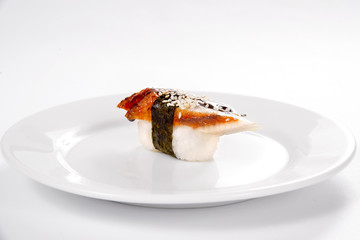 Sushi with smoked eel on a white plate on a white background.