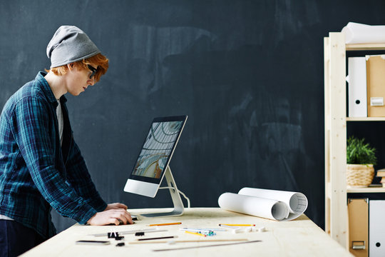 Side view portrait of young red haired engineer using modern computer standing at workplace with blueprints and assorted supplies against blackboard background in office
