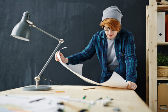 Portrait of young creative red haired man wearing beanie hat and glasses standing at desk while working with blueprints against blackboard background in office