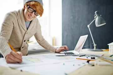 Portrait of smiling young red haired designer wearing glasses and beanie hat working in office: leaning on desk drawing floor plan and using laptop