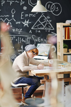 Young red haired man wearing beanie hat and glasses busy drawing schemes at desk in college class against blackboard with scientific formulas written in chalk