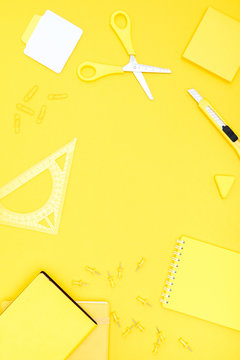 Flat lay of yellow office supplies with copy space on yellow