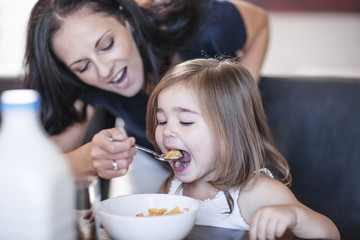 Mother feeding daughter breakfast cereal at table