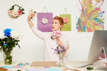 Pretty young floral designer with pink flowers in hand taking selfie against colorful studio wall decorated with abstract painting