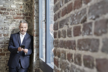 Businessman at a brick wall checking cell phone