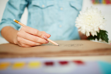 Close-up shot of female hands holding fresh white chrysanthemum and making sketch with pencil, blurred background